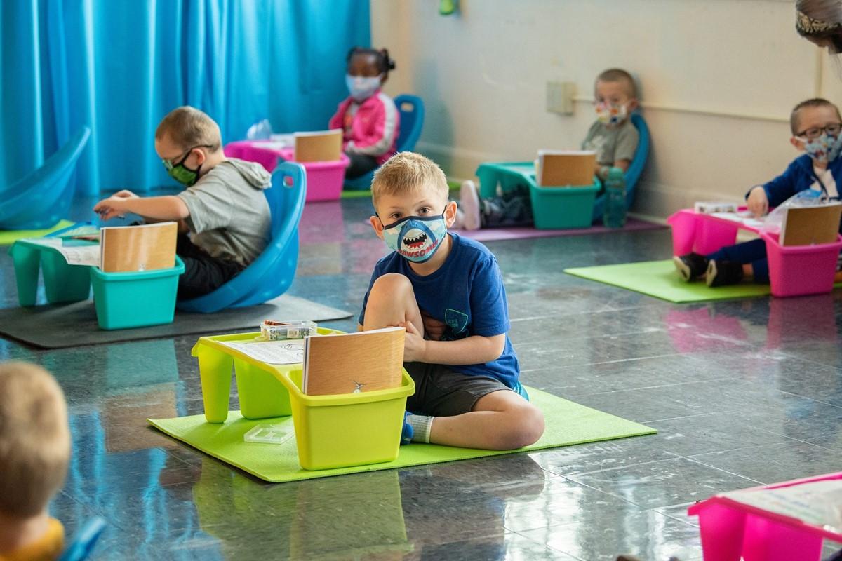 Kindergarten student sitting at desk wearing mask
