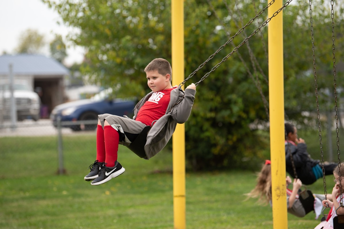 Elementary School Student playing on the playground swings