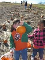 Students holding a small pumpkin