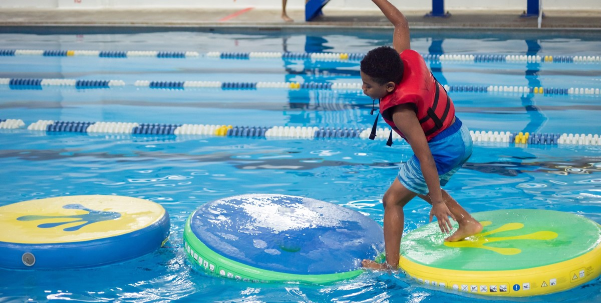 Elementary school student slipping on an aquatic obstacle course, about to fall into water