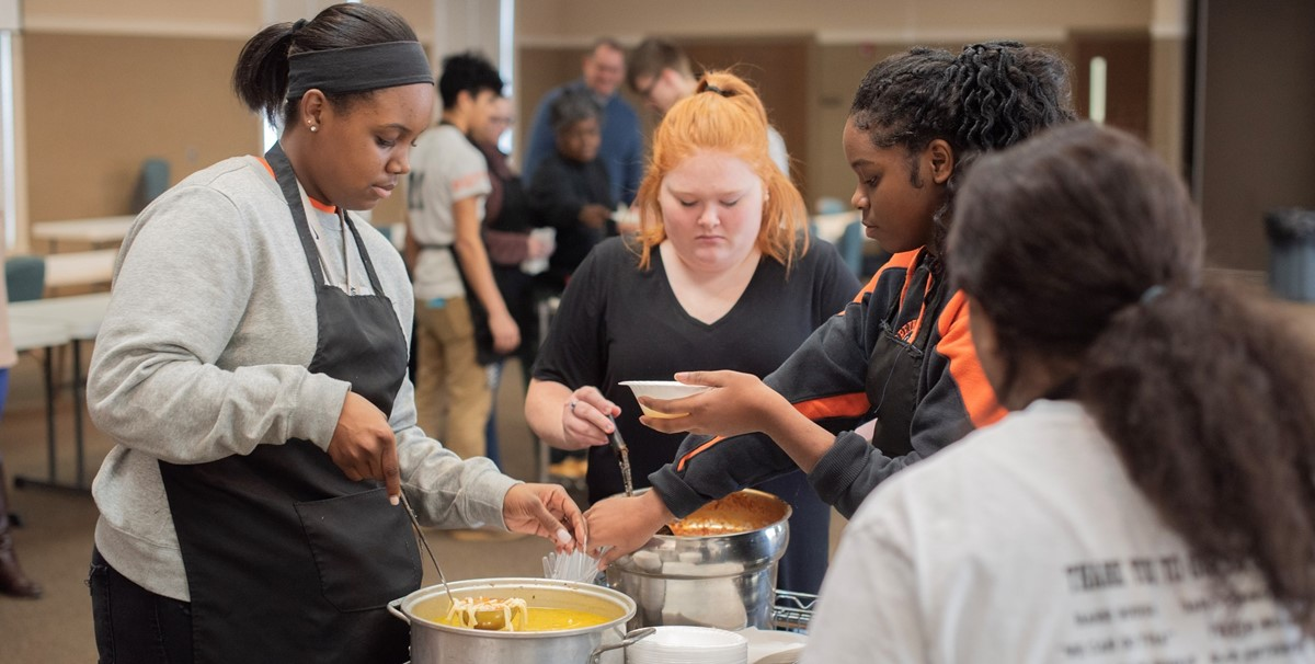 high school students preparing lunch for younger students
