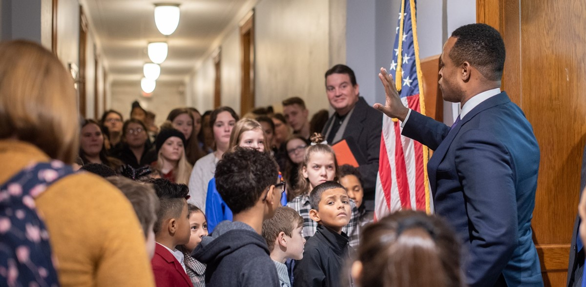 Students listening to a government official speak while standing in a hallway